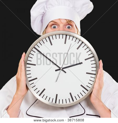 worried chef hiding behind a clock against a black background