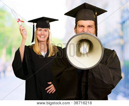 Male And Female Graduate Students With Diploma And Yelling On Megaphone