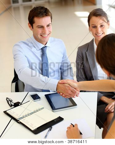 Business associates shaking hands in office
