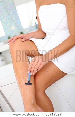 Woman in bathroom shaving her legs