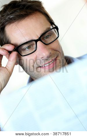 Man with eyeglasses reading newspaper