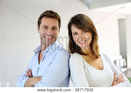 Portrait of married couple standing with arms crossed