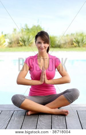 Brunette girl doing yoga exercises by pool