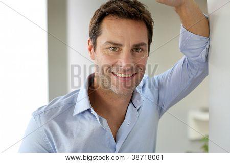 Porträt von schön und glücklich Mann stützte sich auf Wand