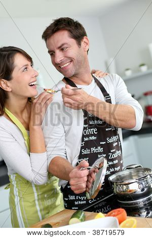 Man preparing dinner and making her wife taste the food