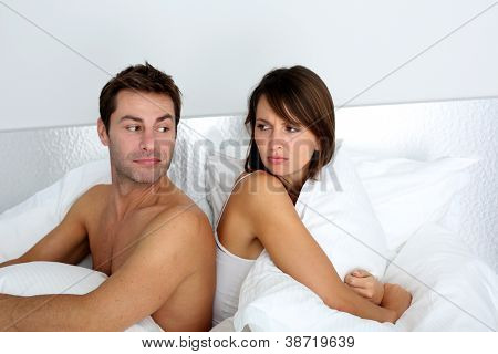 Couple sitting back to back in bed, arguing
