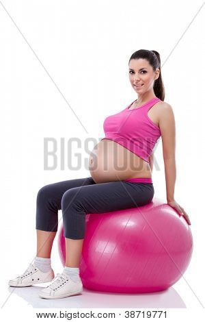 pregnant woman sportswear with large belly  sitting on fitness ball