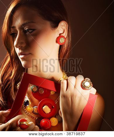 Photo of beautiful girl wearing stylish colorful accessories, closeup portrait of pretty woman in luxury jewelry isolated on brown background, glamour young lady, fashion and style concept