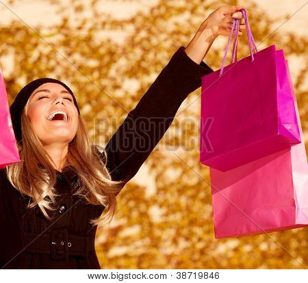 Photo of attractive woman expressing joy of her new purchase, happy good looking girl with pink shopping bags walking in autumn park, money spending and  antistress concept, autumnal sale