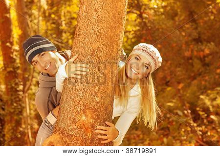 Photo of happy young family having fun in autumnal woods, closeup portrait of cute cheerful couple peeking from behind a tree outdoors, beautiful golden autumn season, love concept