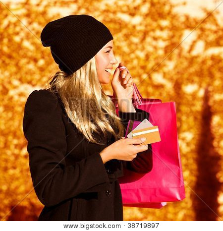 Photo of cute blond girl with pink shopping bag, side view of pretty woman holding paper present bag, beautiful happy shopper over autumn yellow foliage background, seasons sales