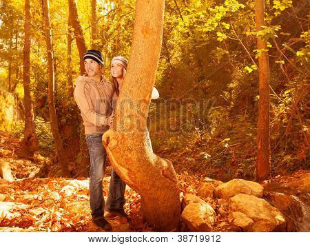 Picture of happy pretty youth enjoying beautiful autumn woods, cute woman and handsome guy wearing stylish warm hats, young family hugging in fall park, romantic relationship, love concept