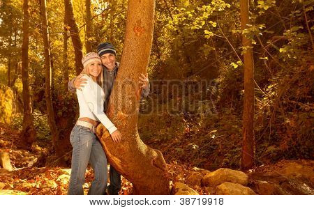 Photo of young lovely family hugging in the forest, happy couple enjoying autumn nature, autumnal holidays, loving relationship, pretty girl with nice guy walking in autumn park, love concept