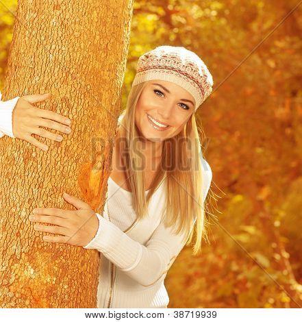 Photo of cute happy girl in autumnal park, closeup portrait of sweet blonde woman wearing stylish beret, attractive female hugging tree trunk in beautiful golden autumn woods