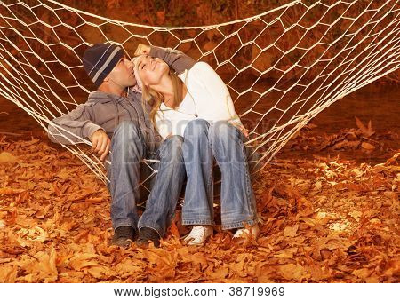 Image of happy couple swinging in hammock, young family having fun in autumn park, best friends resting outdoors, cute lovers hugging on autumnal garden on backyard, love concept