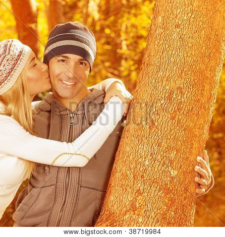 Picture of happy family spending fun time together in beautiful autumn park, closeup portrait of husband and wife kissing, young adult couple enjoying outdoor, love and joy concept