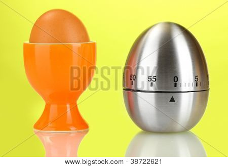egg timer and egg in orange stand on blue background