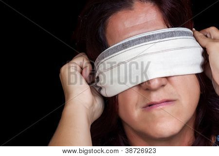 Portrait of a serious woman covering her eyes with a handkerchief to avoid seeing isolated on black (useful to illustrate gender violence or discrimination)
