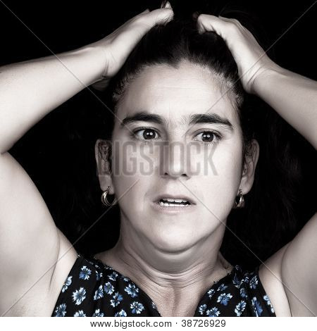 Black and white portrait of a stressed and depressed woman with her hands on her head and a very sad face isolated on black with space for text