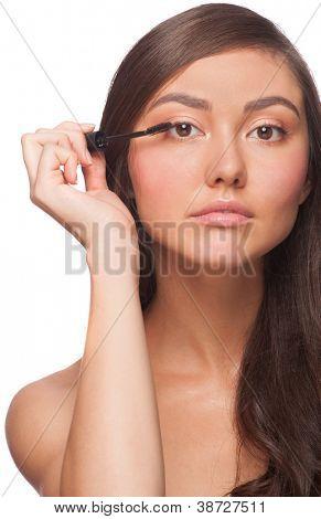 Beautiful woman applying mascara on her eyelashes, isolated on white background