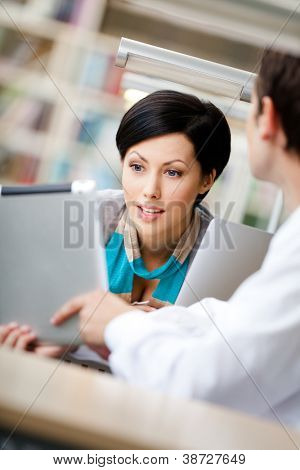 Woman communicates with man showing her something in the tablet sitting at the table at the library