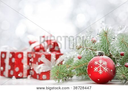 Closeup of Christmas ball with pine branch and gifts on abstract background.