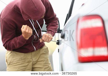 Anzeigen der Schattenseite eines Autos mit einem Mann in einem Kapuzen-Top Einbruch in ein Auto mit einem Schraubenzieher in der Reihenfolge