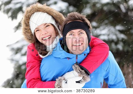Winter couple happy doing piggyback in winter snow forest. Cheerful smiling young interracial couple having fun outside piggybacking. Asian woman, Caucasian man.