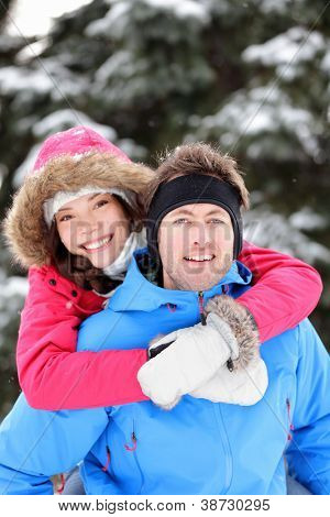 Young excited happy winter couple doing piggyback having fun outside in winter snow forest landscape. Happy young interracial couple, Caucasian man, Asian woman.