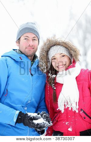 Couple in winter portrait. Young interracial couple smiling looking at camera outside in snow winter forest.