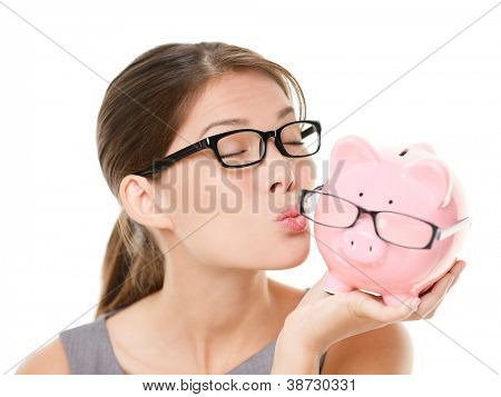 Glasses sale concept. Happy woman kissing piggy bank wearing eyewear glasses. Mixed race Asian Chinese / Caucasian female model isolated on white background.