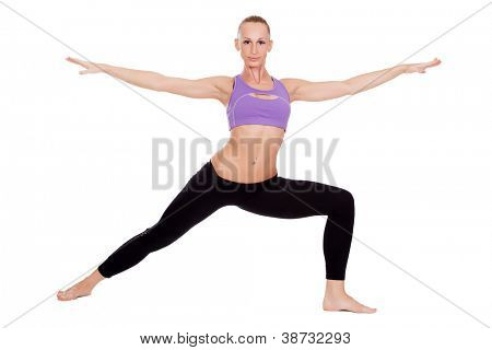 Young yoga woman doing warrior pose on white background