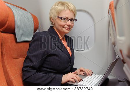 smiling businesswoman posing with laptop on the board of plane
