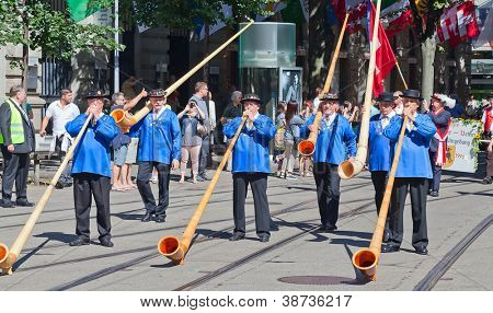ZURICH - AUGUST 1: Swiss National Day parade on August 1, 2012 in Zurich, Switzerland. Musicians with alphorns playing traditional music.