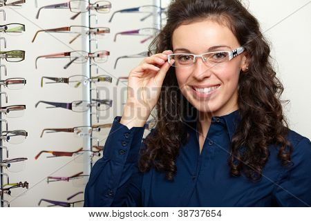 Young attractive smiling woman at optician with glasses, background in optician shop