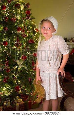 Vintage little girl in victorian white dress near the christmas tree