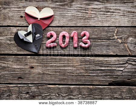 Symbolic male and female heart shapes with 2013 numbers. On old vintage wooden background.