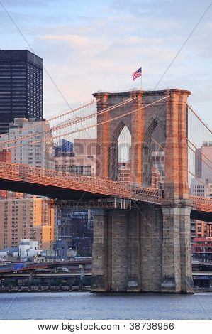 Brooklyn Bridge mit niedrigeren Manhattan Skyline am Morgen mit bunten Wolken über East River in N