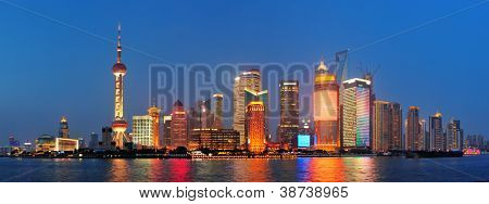 Urban skyscrapers in Shanghai at night over river