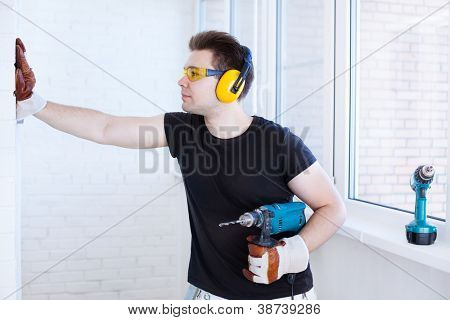 Man worker with drill. Bright white colors.