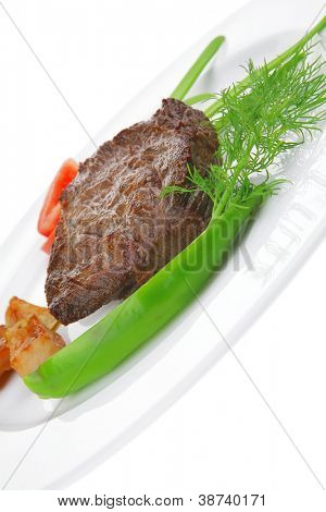 business lunch meat savory : grilled beef fillet mignon on white plate with tomatoes apples and pepper isolated over white background