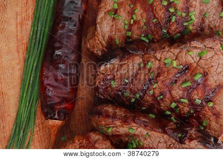 business lunch grilled beef meat on wooden plate with chives and thyme isolated on white background