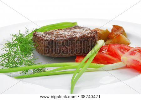 business lunch meat savory : grilled beef fillet mignon served on white plate isolated over white background with chili pepper and tomatoes