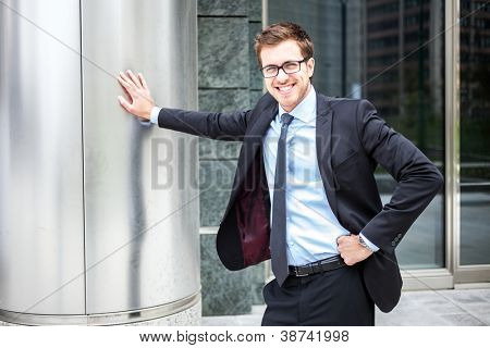 Smiling handsome businessman leaning on a metal column