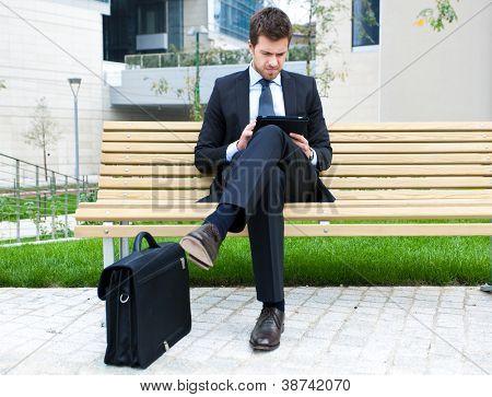 Joven empresario utiliza una tableta en un banco en la ciudad