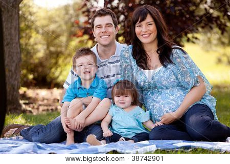 Portrait of a young beautiful family with pregnant mother