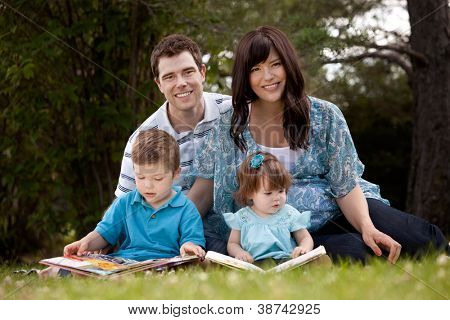 Happy young family with pregnant mother sitting and reading in park