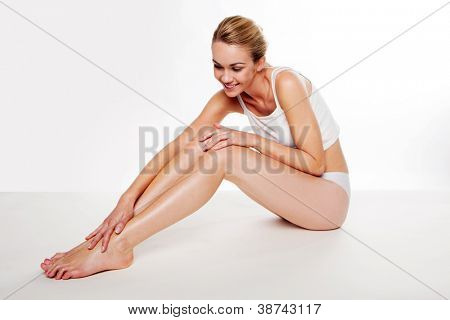 Beautiful blonde woman sitting on the floor caressing her smooth legs after waxing them