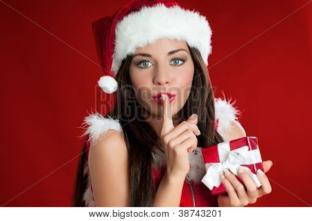 Santa Claus woman holding a present and carrying it secretly for Christmas