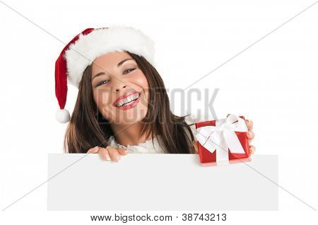 Smiling Christmas girl holding a gift and a white board ready for your text, isolated on white background